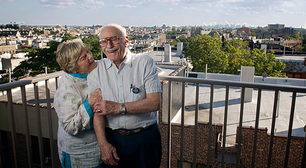 An older man wearing glasses cheerfully stands next to his wife on their balcony at The New Jewish Home Kittay apartments