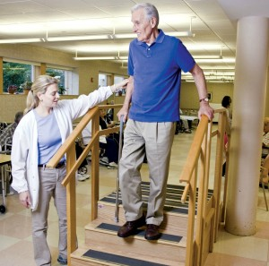 Older man in the New Jewish Home Short-stay rehabilitation program walks down stairs with the help of a physical therapist.