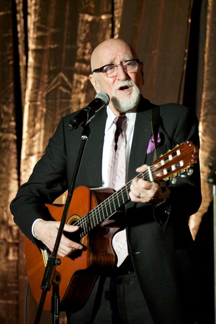 An older bald man with a beard and glasses plays the guitar and sings at The New Jewish Home eight over 80 event