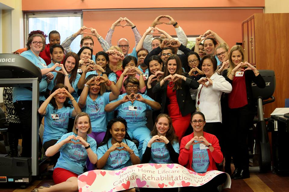 Employees of the New Jewish Home pose, making hearts with their hands and a poster stating,