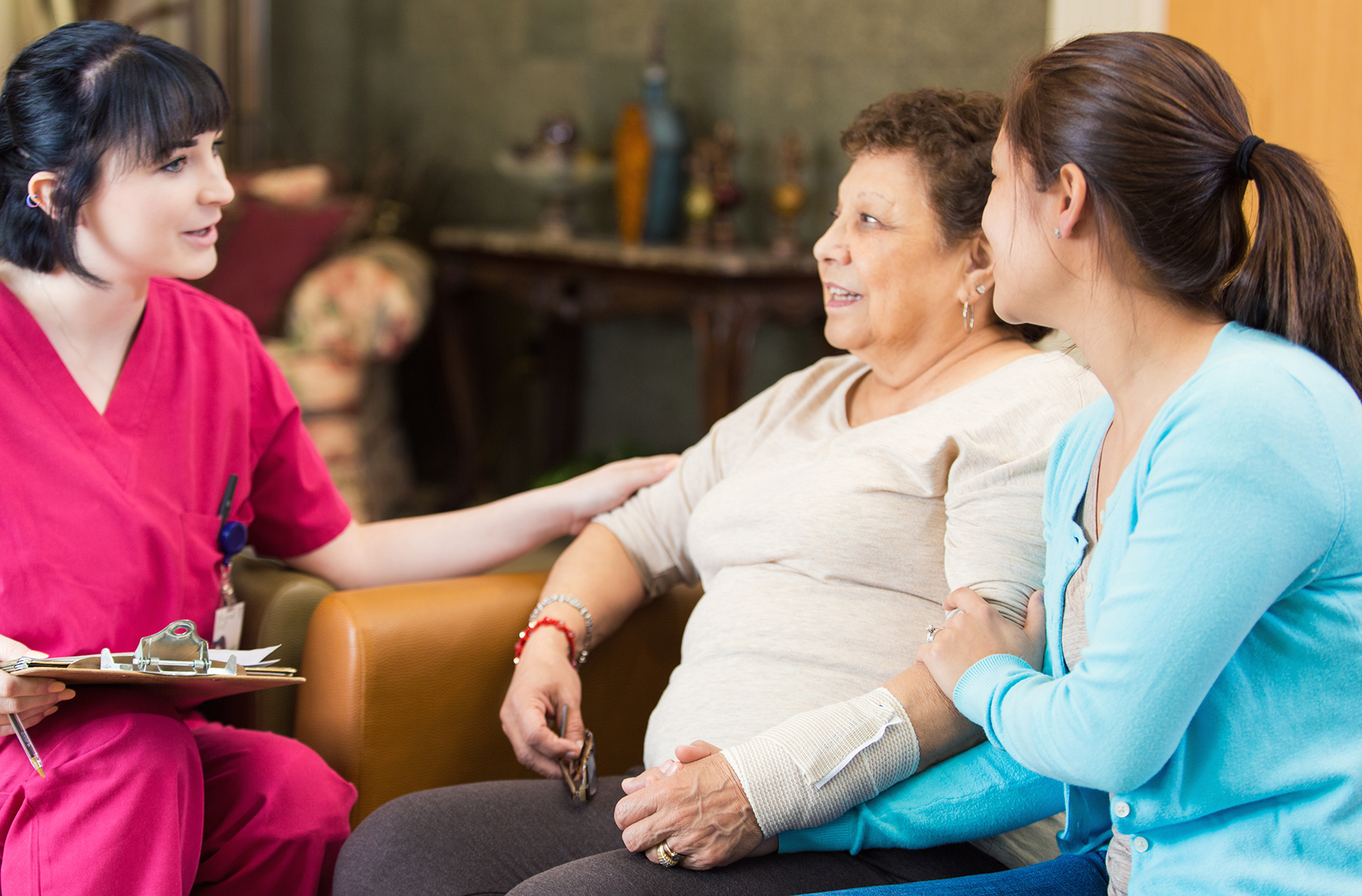 A nurse at the New Jewish Home talks with a Hispanic female patient about her diagnosis as her granddaughter listens along
