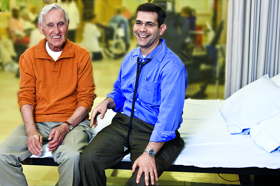 A resident from The New Jewish Home wears an orange sweater and sits next to his doctor who is wearing a blue shirt