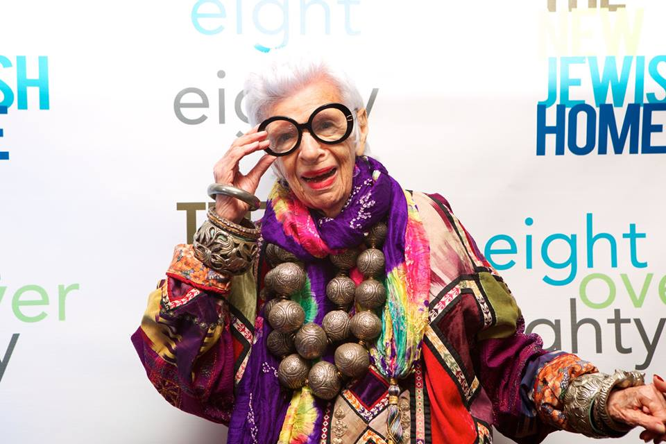 An older woman with white hair and large round glasses posses for a picture in an eccentric and brightly draped outfit.