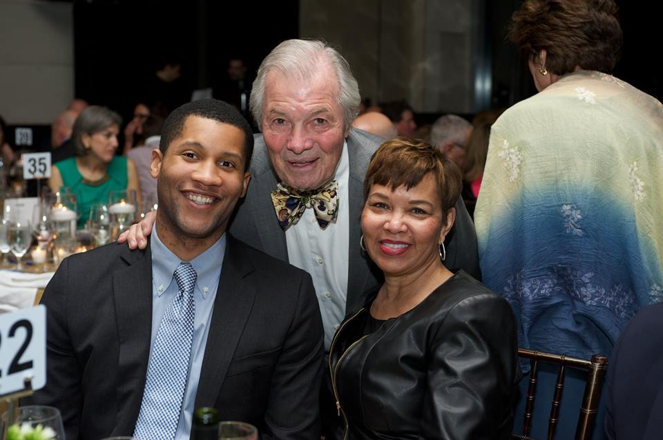 an older man in a suit leans in for a picture with an African American couple at the New Jewish Home eight over 80 gala event