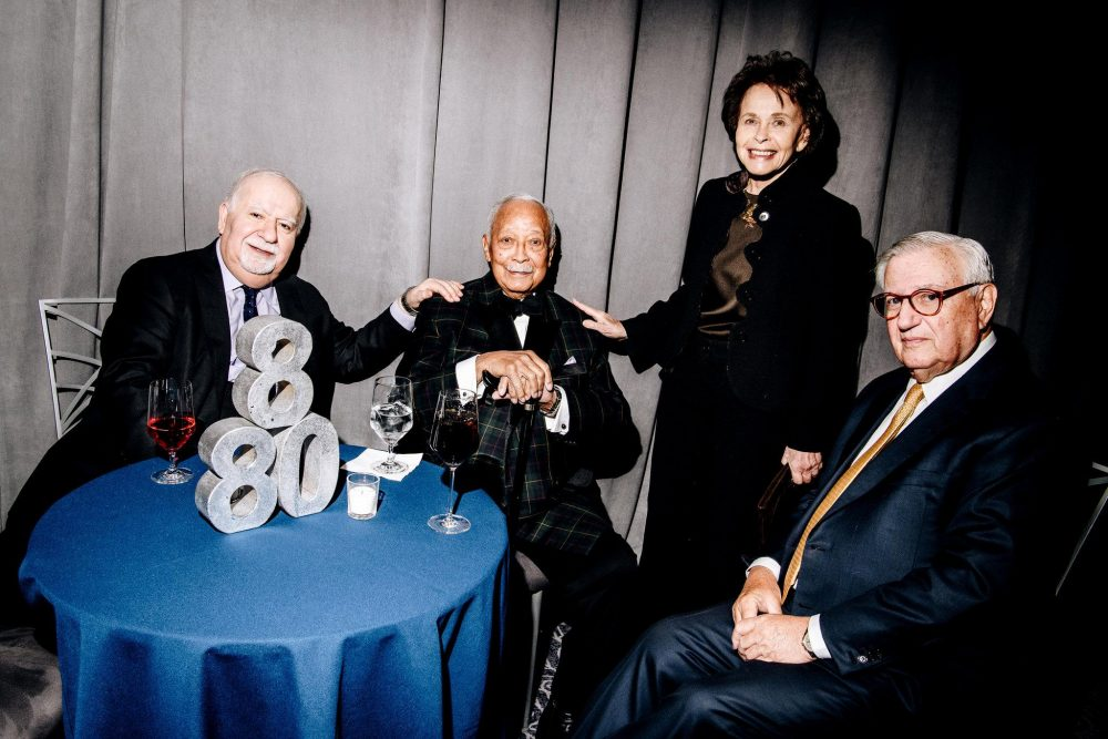 Three older men in black suits and a woman in a black dress sit at a blue table at The New Jewish Home eight over 80 gala