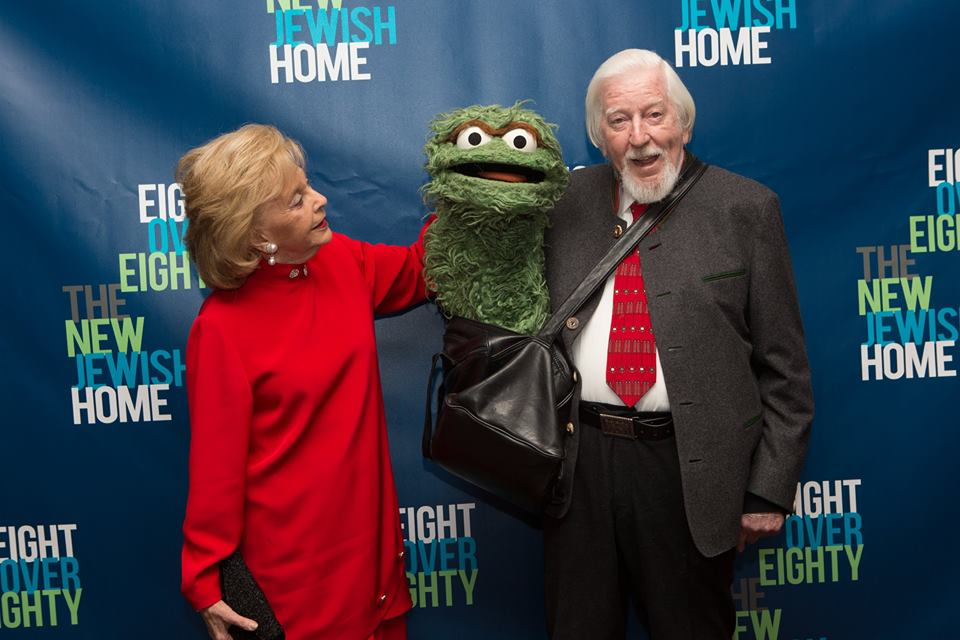 An older woman in a red dress places her hand on the shoulder of a bearded man wearing a grey suit holding Oscar the puppet