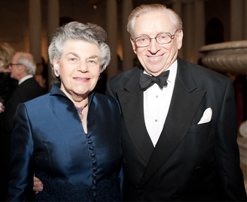 Older woman with grey hair wearing a blue dress stands next to an older man with graying hair and glasses wearing a black tux