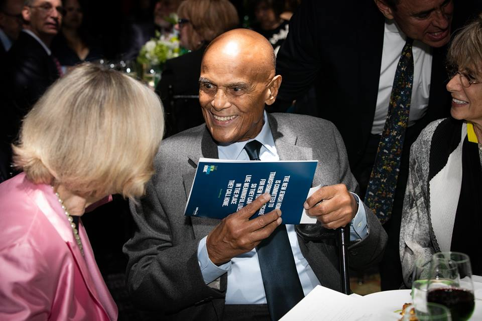 A bald African American man in a grey suit holds a pamphlet from The New Jewish Home at the Eight over Eighty Gala Event