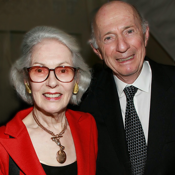 An older woman in a red jacket and glasses with an older balding man in a black suit at the New Jewish Home 8 over 80 gala