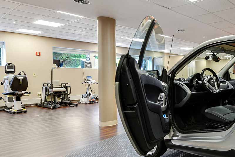 Well-lit state of the art gym including a full-size car at the New Jewish Home Short-stay Rehabilitation Center in Manhattan