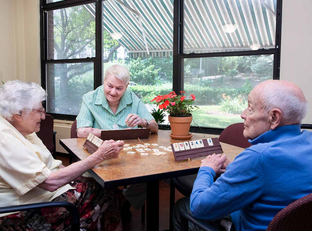 Three older adults sit at a table with a vase of red flowers by a window as they play dominoes at the New Jewish Home.