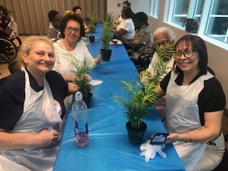 Clients at The New Jewish Home's Adult Day Health Care program show off their newly potted bamboo plants