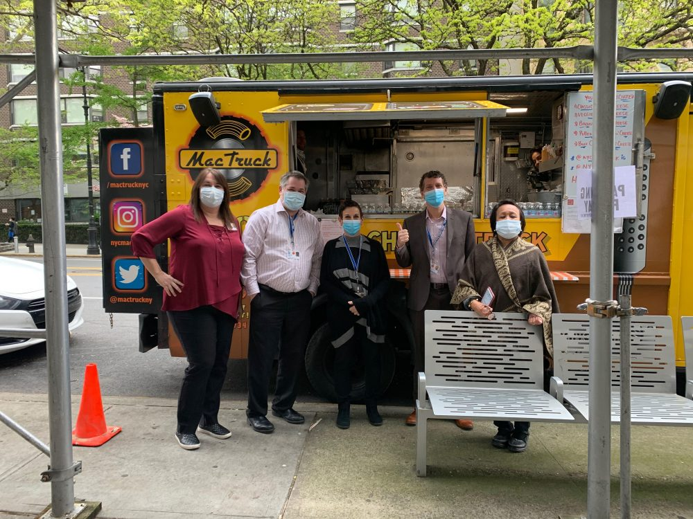Health care workers standing in front of food truck