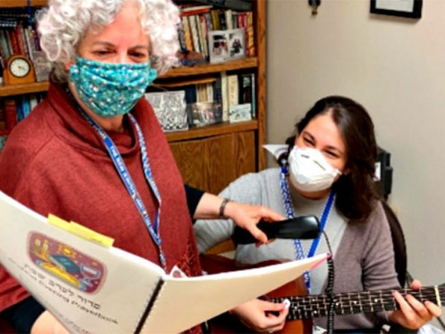 Cantor Laura Stein and Rabbi Sandy Bogin lead Shabbat worship services behind loudspeaker